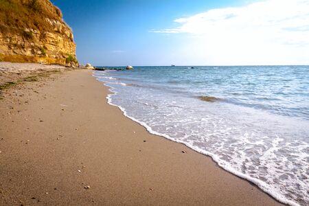 Sea is breaking foamy waves on the sandy beach, coast with rocky cliff.