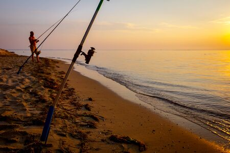 Man is catching fish from the sandy beach with a few fishing rods, morning over Mediterranean sea.