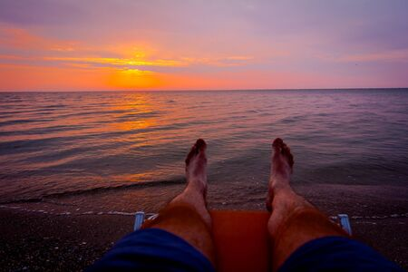 Man's legs until is sunbathing by lying carefree in lounger next to the coastline, on public beach.