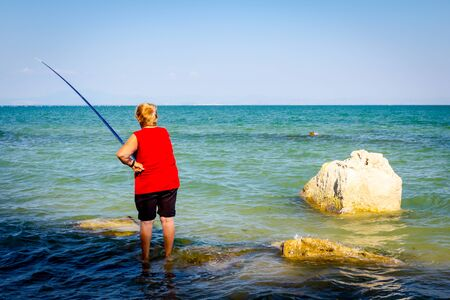 Senior woman is standing in the sea and fishing. Banque d'images