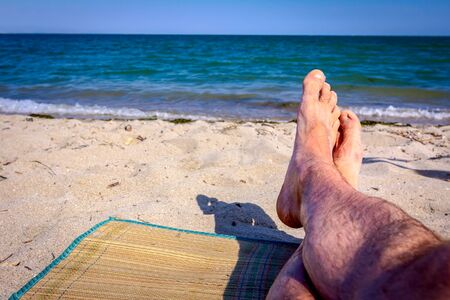 Mans legs until is sunbathing by lying carefree on mat next to the coastline, on public beach.