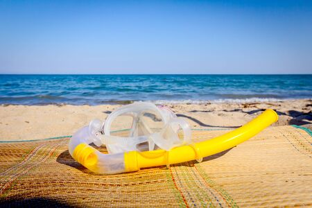 Diving mask and snorkel breather tube are placed on mat at the sandy beach. Imagens