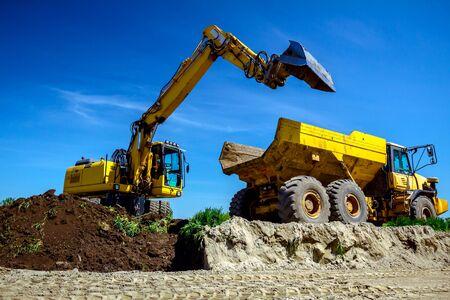 Großer Bagger füllt einen Muldenkipper mit Erde auf der Baustelle, Projekt läuft.