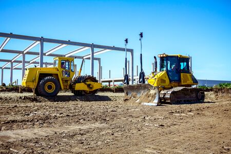 Bulldozer is pushing ground, leveling, equates and road roller with spikes is compacting soil on building site.