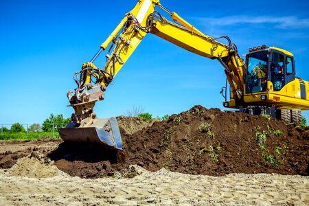 La excavadora de ruedas está excavando suelo en el sitio de construcción, proyecto en curso.