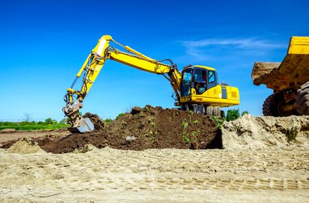 Big excavator is filling a dumper truck with soil at construction site, project in progress.
