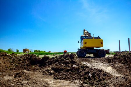 Wheeled excavator is excavating soil at construction site, project in progress.