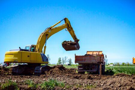 Gran excavadora está llenando un camión volquete con tierra en el sitio de construcción, proyecto en progreso.