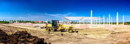 Panorama showing the grader is leveling a landscape, transform into urban area. View on construction site.