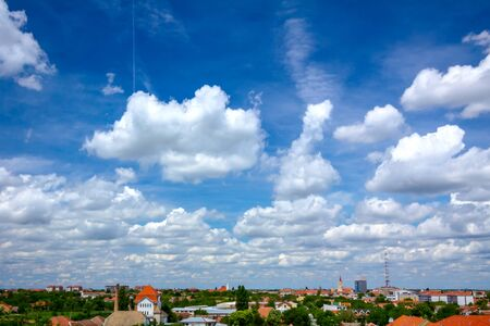 Scenic view is on beautiful blue sky with white fluffy clouds and cityscape in the distance.