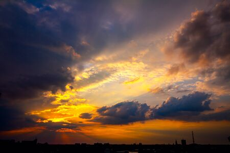 Scenic view is on beautiful dark sky with cumulus clouds at sunset and silhouette of city in the distance.