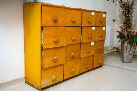 Old wooden textured drawers with handles for folders and files of medical record, patient information.