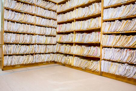 Shelves are full with folders and files of medical record, patient information.