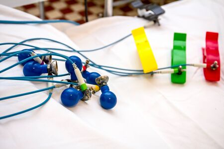 ECG or EKG electrodes for electrocardiogram records patient heartbeats on bed in hospital.