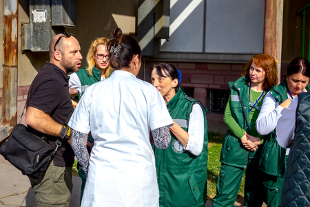 Zrenjanin, Vojvodina, Serbia - October 19, 2018: Photographer is talking with group of medical personnel about photo season in their clinic.