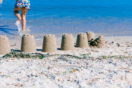 Children's sand figure made with bucket mold, castle on the beach, tower shapes.