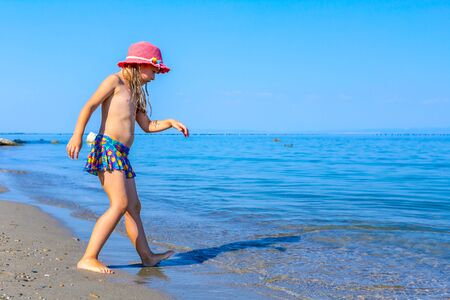 Young woman, restless child in cute summer hat is dancing and splashing in shallow water, sandy beach at sea shore.
