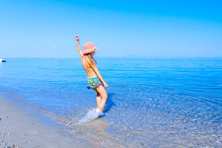 Young woman, restless child in cute summer hat is dancing and splashing in shallow water, sandy beach at sea shore. Standard-Bild