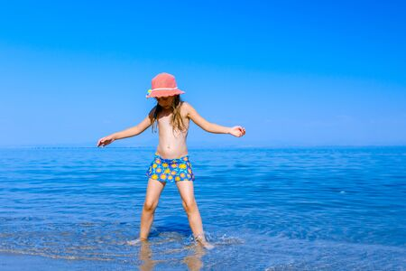 Young woman, restless child in cute summer hat is dancing and splashing in shallow water, sandy beach at sea shore. Banque d'images