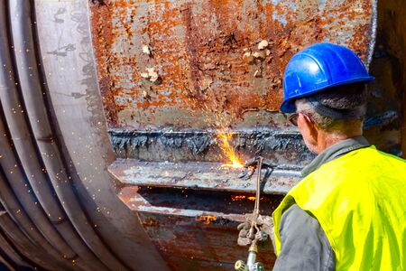 Worker is cutting manually old metal construction using gas mixture of oxygen and acetylene, propane. Standard-Bild