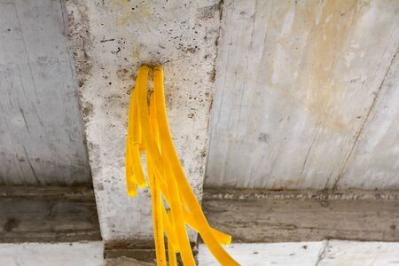 Bundle of yellow protective ribbed plastic hoses for cables are coming out from concrete ceiling. Archivio Fotografico