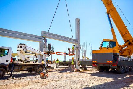 Mobilkran ist in Betrieb und Arbeiter montiert Betonbalken an hoher Stelle. Höhenarbeiter legt Fachwerk auf Gebäudeskelett.