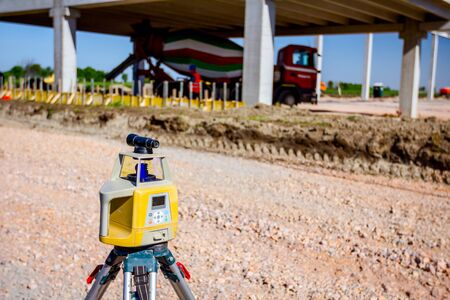 Total center device on tripod with laser for leveling other devices to level construction site.
