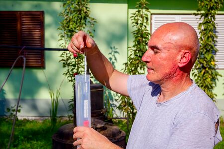 Man is using glass alcoholmeter for determining the amount, concentration of alcohol in liquor. Sample is placed in laboratory graduated cylinder.
