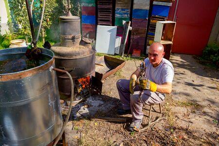 Mann wirft trockene Äste in den Feuerraum einer hausgemachten Brennerei, die Mondscheinschnaps, alkoholische Getränke, herstellt.