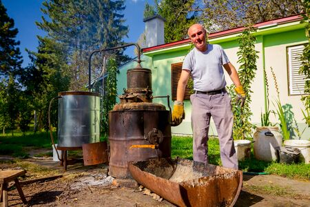 Man is manually turning lever to mix fruit marc in boiler of homemade distillery made of copper, making moonshine schnapps, alcoholic beverages such as brandy, cognac, whiskey, bourbon, gin, scotch.