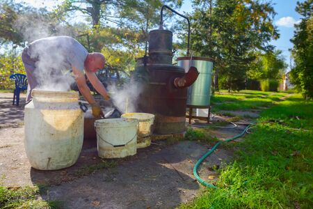Man is unloading boiler of homemade distillery made of copper to release used fruit marc, making moonshine schnapps, alcoholic beverages such as brandy, cognac, whiskey, bourbon, gin, and scotch.
