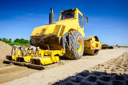 Vibration plate compactor is mounted to the steamroller, compacting sand at road construction site. Foto de archivo