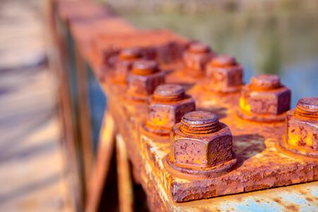 Detail of steel construction with old rusty screws on the fence of the bridge.