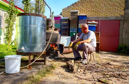 Man throws dry branches into the firebox of a homemade distillery making moonshine schnapps, alcoholic beverages.