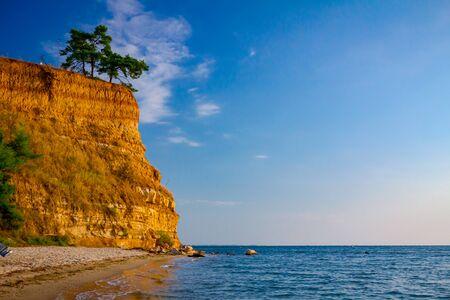 Sea is breaking foamy waves on the sandy beach, coast with rocky cliff.  Foto de archivo