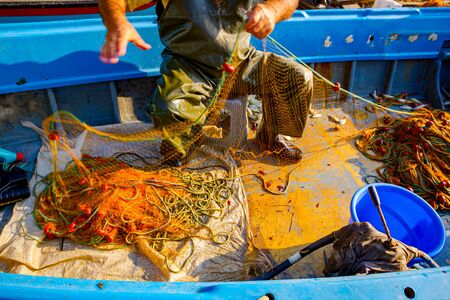 Fisher in rubber trousers and boot siting in his boat and pile up fishing net for angling at open sea.