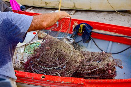 Fisherman is pile up fishing net and prepare for his next angling.
