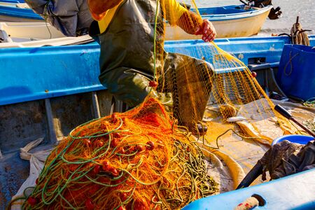 Fisher in rubber trousers and boot is sitting in his boat and pile up fishing net for angling at open sea.