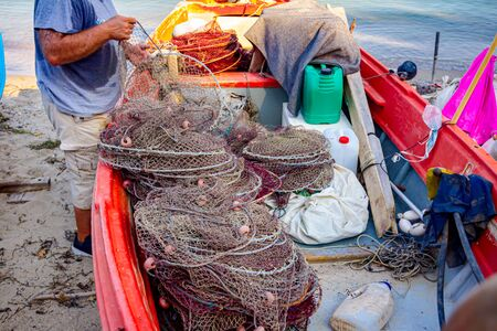 Fisherman is taking out fish from net and prepare for his next angling.