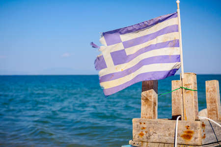 An old torn Greek flag flutters in the wind, set on a small wooden chair, open sea in the distance.