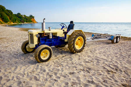 Tractor with empty trailer is parked on the sandy beach, waiting for transport boats.