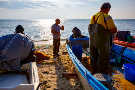 Two fishermen on the beach, one in the boat and the other next to the boat, pile up fish net for next angling.
