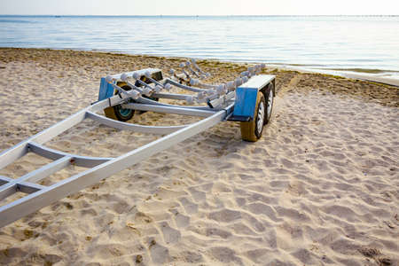 An empty trailer is parked on the sandy beach, waiting for transport boats. Banque d'images