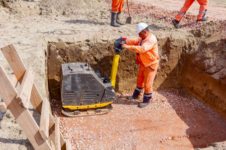 Wooden ladders for worker to exit after compacting gravel with vibration plate compactor machine in square trench.