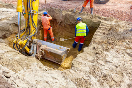 Workers are using shovels for realign excess of ground to correct trench measure. Stock Photo