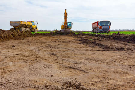 Big excavator is filling two dumper trucks with soil at construction site, project in progress.