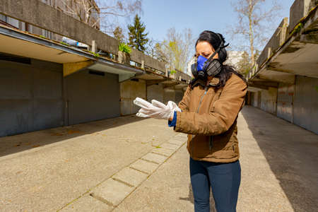 Woman with filter mask on her face puts rubber gloves on her hands for protection against virus COVID-19, Corona. Reklamní fotografie