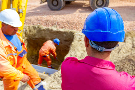 View from behind on construction worker, foreman, with safety blue helmet looking at worker who is using shovel to correct trench measure.