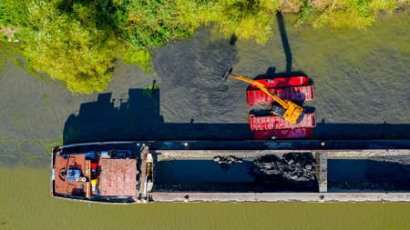 Above top view on excavator dredge is dredging, working on river, canal, deepening and removing sediment, mud from riverbed in a polluted waterway.