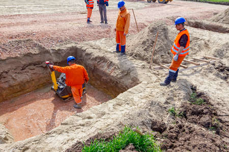 Worker is compacting gravel with vibration plate compactor machine in square trench.